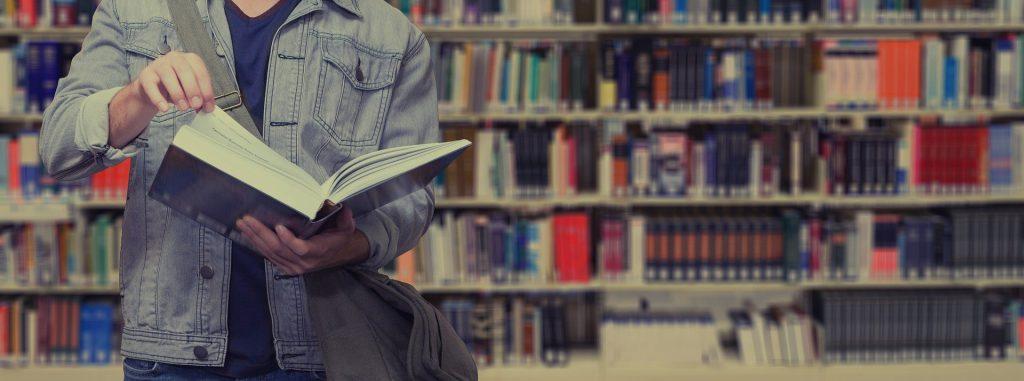 En ung person i jeansjacka håller i en öppen bok, bläddrar i boken. I bakgrunden syns bokhyllorna i ett bibliotek.